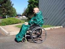 Photo représentant une personne en fauteuil roulant manuel et portant une cape verte de pluie