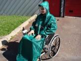 Photo d'une personne en fauteuil roulant avec une cape de pluie verte