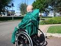 Utilisateur d'une cape de pluie verte, vue de dos sans la capuche, les poignées du fauteuil passent à travers la cape
