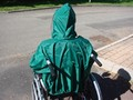 Utilisateur d'une cape de pluie verte, vue de dos avec la capuche, les poignées du fauteuil passent à travers la cape